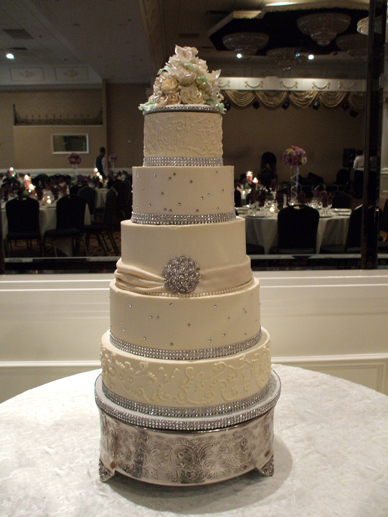 5 tier ivory wedding cake with diamond studs and buttercream scrolls and diamond ribbons for the borders
