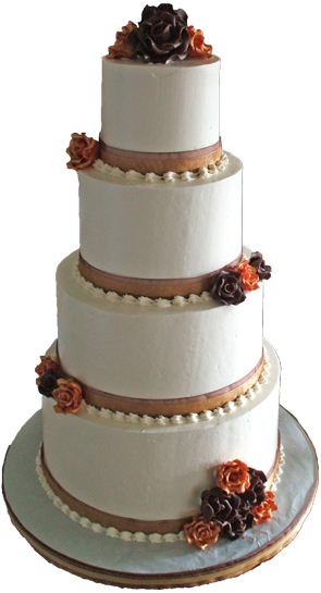 4 tier buttercream wedding cake with brown and gold ribbons, brown and gold chocolate flowers and buttercream shell borders