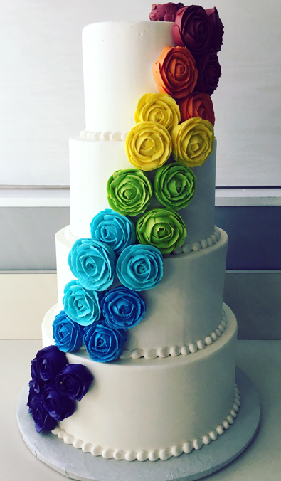 4 Tier buttercream wedding cake decorated with tie dye rain bow buttercream flowers