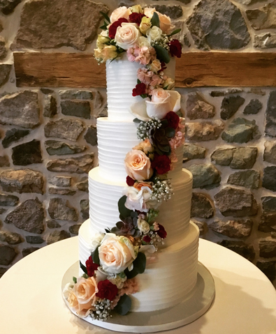 4 Tier rustic textured buttercream wedding cake decorated with cascading fresh flowers