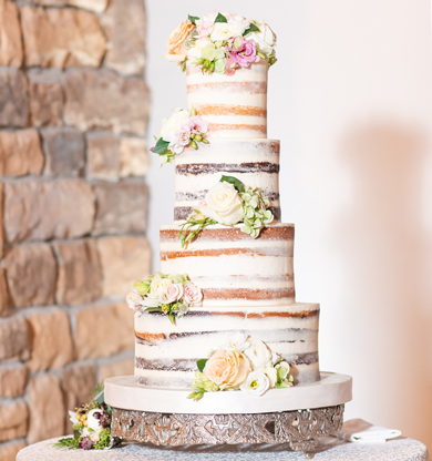 4 Tier semi naked wedding cake decorated with fresh flowers