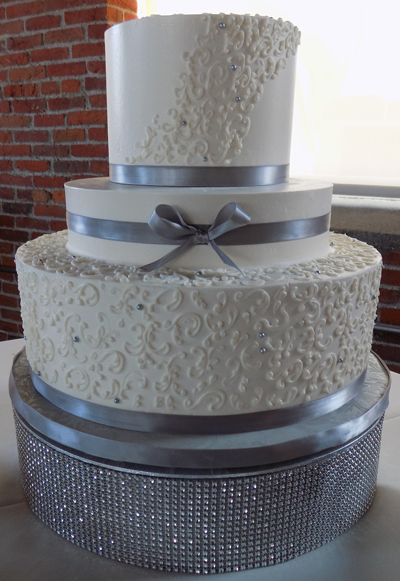 3 tier buttercream wedding cake decorated with small buttercream scrolls silver sugar pearlsdragees silver ribbons and placed on a blingdiamond wedding