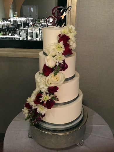 4 Tier buttercream wedding cake decorated with an assortment of cascading red and white fresh flowers delivered at Heritage Hills Gold Resort York PA