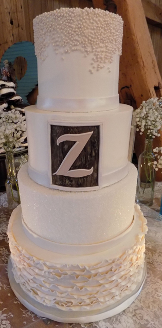 Four tier buttercream wedding cake decorated with sugar pearls, sugar crystals, fondant frills and ribbons, as well as a wooden fondant frame with initial of bride and groom's last name. Cake was delivered at the Ironstone Ranch in Elizabethtown PA