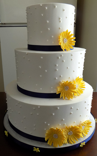 3 Tier buttercream wedding cake, decorated with Swiss dots, navy blue ribbons and yellow hand made gum paste sugar daisies, delivered at The Great American Saloon Restaurant in Red Lion PA
