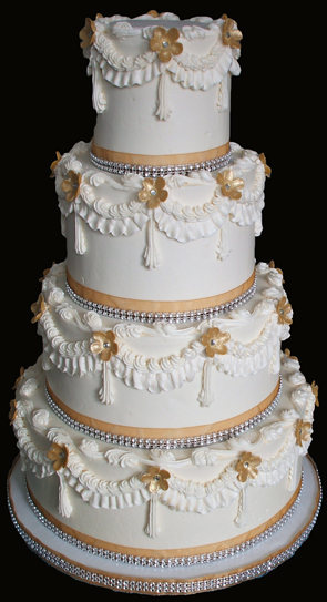 4 tier buttercream wedding cake decorated with gold and diamond bling ribbons and heavy buttercream scallops