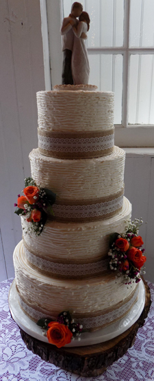 4 Tier textured buttercream wedding cake decorated with burlap and lace ribbons and burnt orange fresh roses delivered at Lauxmont Farms Wrightsville PA