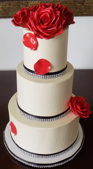 3 Tier marble buttercream wedding cake, filled with raspberry preserve and ganache and decorated with black and bling diamond ribbons