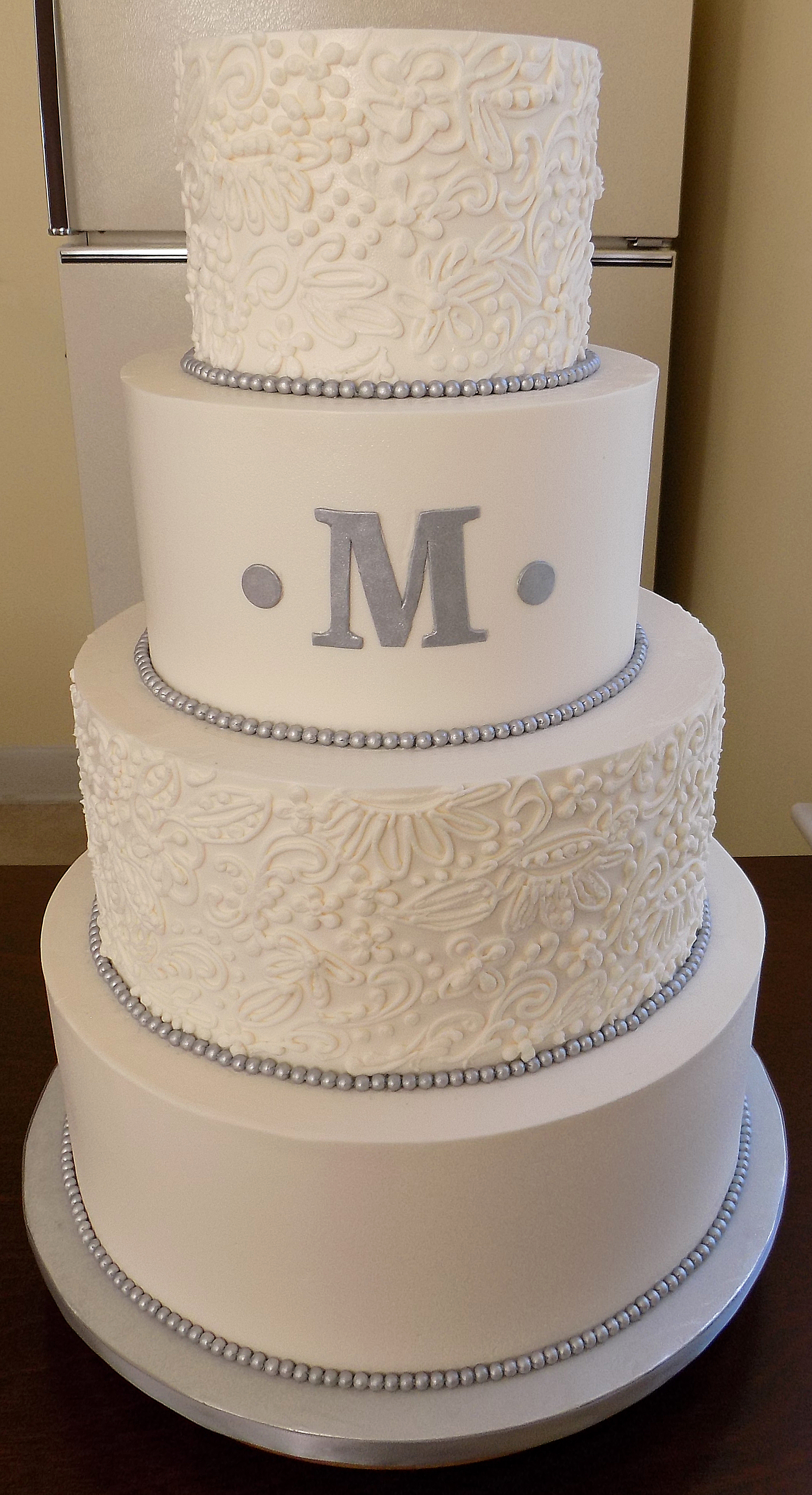 4 Tier buttercream wedding cake, decorated with buttercream lace designs, silver fondant pearl borders and a silver M monogram delivered at Wyndridge Farms Dallastown PA