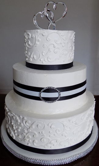3 Tier buttercream wedding cake, decorated with scrolls, black ribbons and diamonds