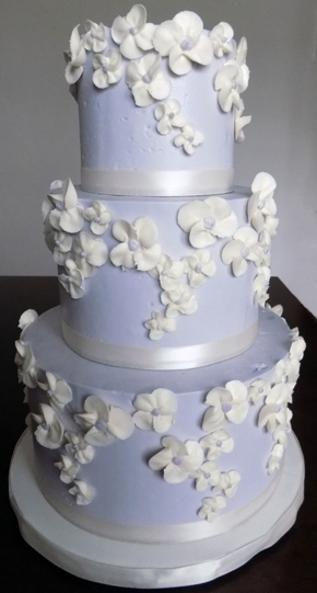 3 Tier buttercream wedding cake, iced in lilac buttercream and decorated with ivory buttercream blossoms