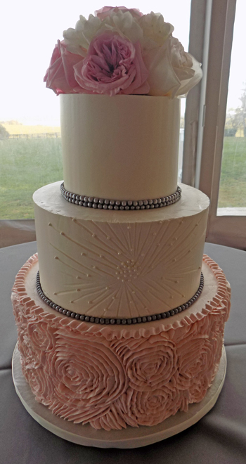 3 Tier buttercream wedding cake, decorated with blush pink buttercream ruffles, buttercream pleats, and charcoal grey fondant pearls and fresh blush pink and white fresh flowers delivered at Lauxmont Farms Wrightsville PA
