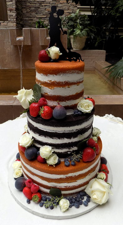 3 Tier truly naked wedding cake decorated with fresh fruit and flowers. Wedding Cakes Eden Resort Lancaster PA