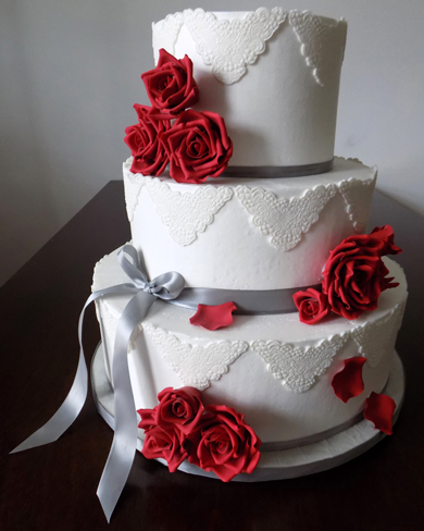 3 Tier buttercream wedding cake, decorated with silver ribbons, white fondant lace appliques and hand made red gumpaste sugar roses. Wedding cake was delivered in Lancaster PA.