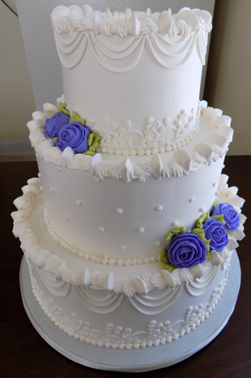 3 Tier buttercream wedding cake, decorated with drop strings, Swiss dots and lilac/light purple buttercream roses delivered at Brookside Park in Dover PA