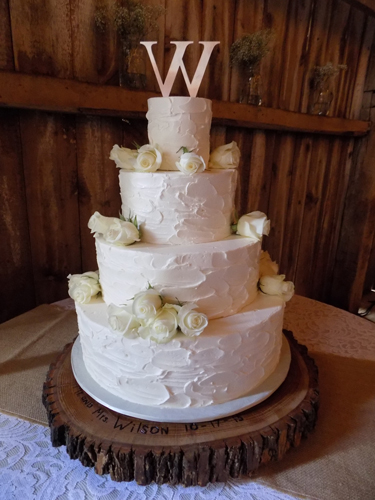 4 Tier rustic textured buttercream wedding cake, decorated with fresh white roses. Wedding cake was delivered at the Pine Ridge Farm in Stewartstown PA.