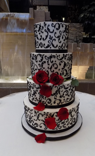 4 Tier buttercream wedding cake, iced in vanilla buttercream and decorated with black buttercream scrolls, fresh red stem roses, rose petals, delivered at the Eden Resort in Lancaster PA