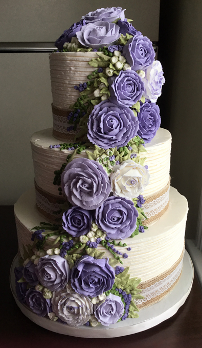 3 Tier rustic textured buttercream wedding cake, decorated with burlap and lace ribbons and an assortment of cascading lilac buttercream flowers with buttercream greenery.