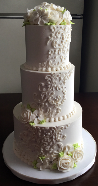 3 Tier buttercream wedding cake, decorated with cascading buttercream scrolls, sugar pearls, buttercream roses and small flowers