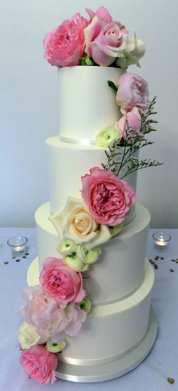 Four tier buttercream wedding cake decorated with an assortment of fresh flowers including roses, peonies and ranunculus - wedding cakes Yoe PA