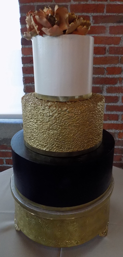 3 Tier ivory, gold and navy blue buttercream wedding cake decorated with edible gold sequins and sugar flowers. Wedding Cakes John Wrights restaurant York PA