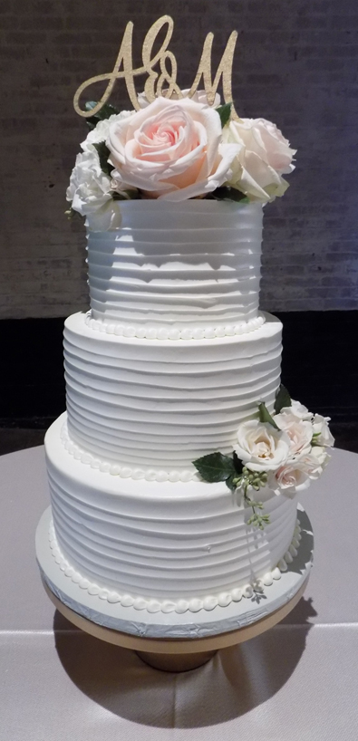 3 Tier rustic textured buttercream wedding cake decorated with fresh flowers. Wedding Cakes at the Bond York PA
