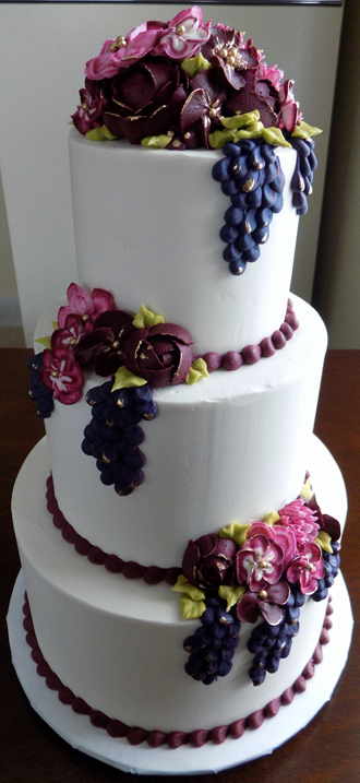 3 Tier buttercream wedding cake, decorated with an assortment of wine colored and burgundy buttercream flowers as well as grape clusted with gold hi-lights<br /> <em>Wedding Cakes York PA</em>