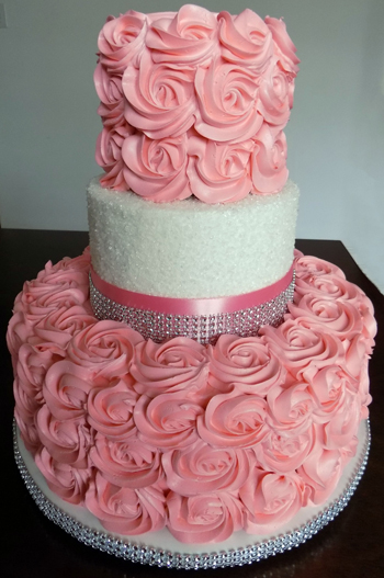 3 Tier buttercream wedding cake, decorated with coral rosettes, sugar crystals and coral and bling ribbons.<br /> <em>Wedding Cakes Lancaster PA</em>