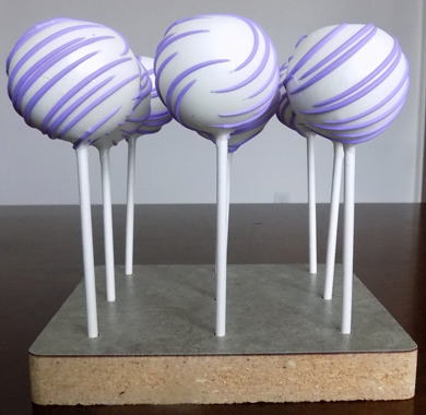 Chocolate raspberry cake pops, dipped in white chocolate and decorated with chocolate lavender stripes