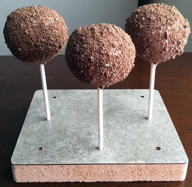 Chocolate cake pops dipped in white chocolate and covered with gold high lighted chocolate shavings