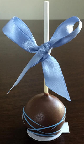 Yellow cake pops dipped in dark chocolate, decorated with light blue chocolate stripe and light blue bows