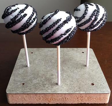 Chocolate cake pops dipped in white chocolate and decorated with black non peril stripes