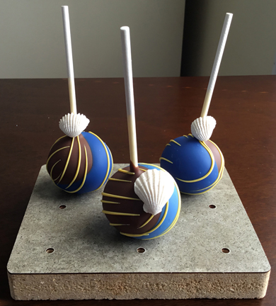 Nautical themed cake pops. Yellow cake pops dipped in dark chocolate and blue chocolate, decorated with yellow chocolate stripes and fondant sea shells