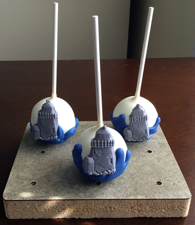 Nautical themed cake pops. Chocolate cake pops dipped in white chocolate, decorated with blue chocolate ocean and silver fondant light houses
