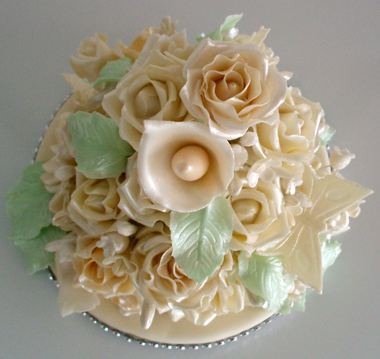 Top view of hand made wedding cake topper of assorted off white flowers