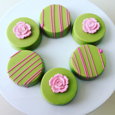 Oreo cookies, dipped in neon green with some decorated with hot pink chocolate stripes and others decorated with pink sugar flowers
