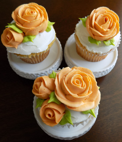 Yellow cupcakes, filled and iced with vanilla buttercream and decorated with orange buttercream roses delivered at the Peter Allen House in Dauphin PA
