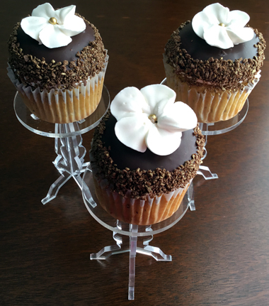 Banana cupcakes, filled with dulce de leche, iced with vanilla buttercream and dipped in dark chocolate ganache and decorated with gold hilighted chocolate shavings