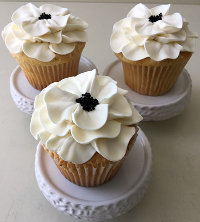 Cupcakes decorated with white fantasy buttercream flowers with black centers