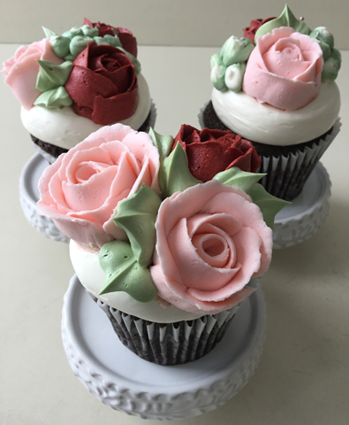 Cupcakes decorated with red and blush buttercream roses and buttercream buds