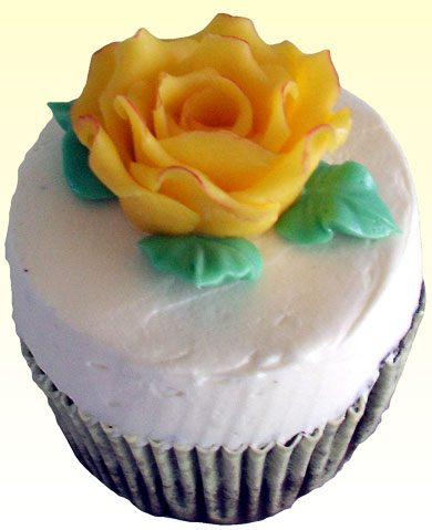 Chocolate cupcakes topped with a yellow rose made of chocolate