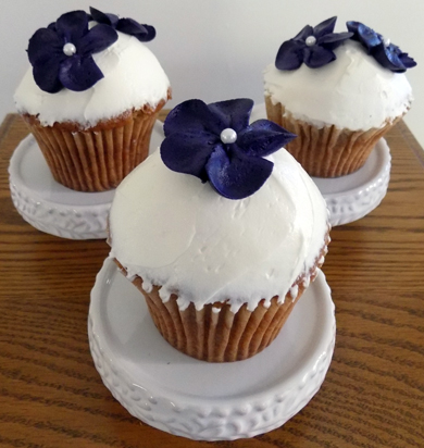 Spice cupcakes filled with cream cheese icing, iced with vanilla buttercream, decorated with deep purple buttercream blossom flowers delivered at Red Lion PA Social Hall