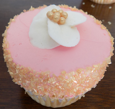 Yellow cupcakes filled and iced with coral vanilla buttercream, decorated with gold sugar crystals and an ivory buttercream flower with a gold acenter
