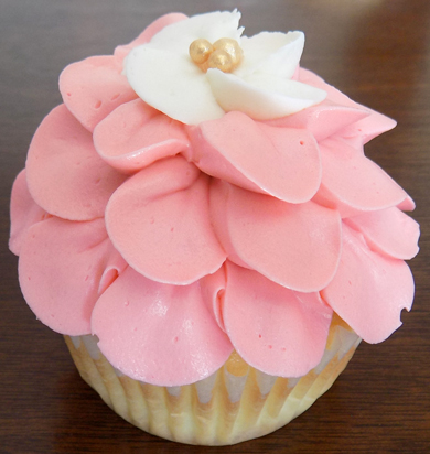 Yellow cupcakes filled with vanilla buttercream icing and decorated with a coral and ivory fantasy buttercream flower