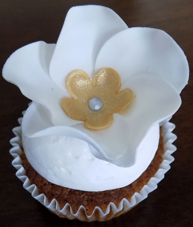 Carrot cupcakes, filled with cream cheese icing, topped with vanilla buttercream and decorated with a gumpaste flower with a gold center
