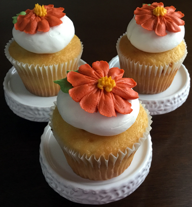 Yellow cupcakes filled with raspberry filling, iced with vanilla buttercream and decorated with burnt orange buttercream flowers delivered at Acorn Meadows in Thomasville PA