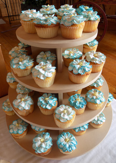 Almond cupcakes, filled with raspberry preserve and decorated with turquoise vanilla buttercream flowers. Cupcakes Monkton MD