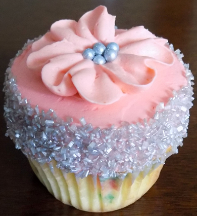 Confetti cupcakes, filled with vanilla buttercream, decorated with silver sugar crystals and coral buttercream flowers