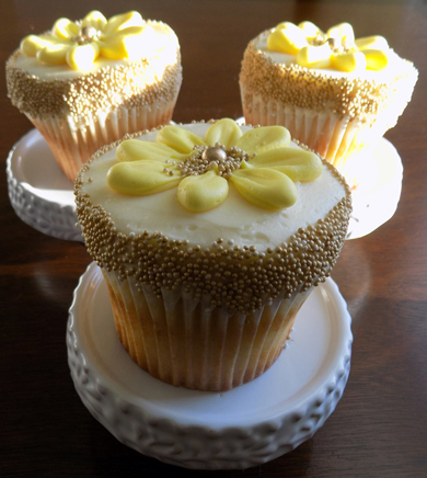 Lemon cupcakes, filled with raspberry filling, iced with lemon buttercream and decorated with gold non perils and yellow buttercream daisies