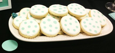 Round sugar cookies, iced with white royal icing with mint green polka dots